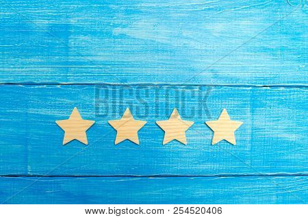 Four Stars On A Blue Background. The Concept Of Rating And Evaluation. The Rating Of The Hotel, Rest
