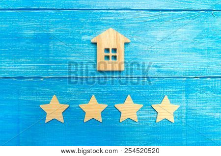 Wooden House And Four Stars On A Gray Background. Rating Of Houses And Private Property. Buying And