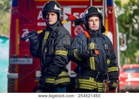 Photo of two firemen with axes in hands near fire engine