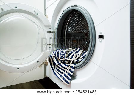 Image of open washing machine with striped cloth