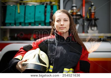 Photo of young firefighter woman staring into camera with long hair next to fire engine