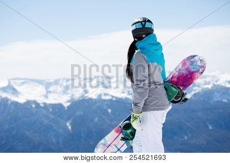 Photo from back of woman tourist helmet with snowboard on background of snowy mountains