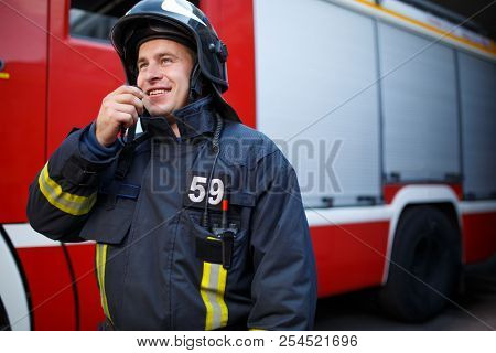 Photo of smiling fireman talking on walkie-talkie with fire engine