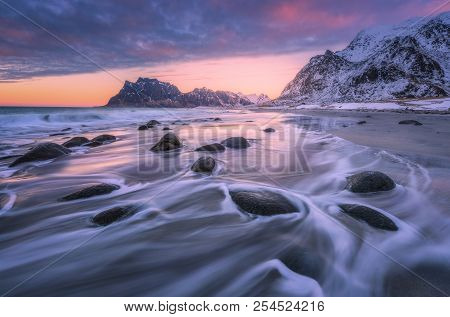 Beautiful Sandy Beach With Stones In Blurred Water, Colorful Cloudy Pink Sky And Snowy Mountains At