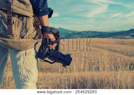Man professional photographer with digital camera walking in tuscany fields. Photo Camera in male hands over summer landscape in Tuscany with fields, blue sky and moutains, Italy, Europe.