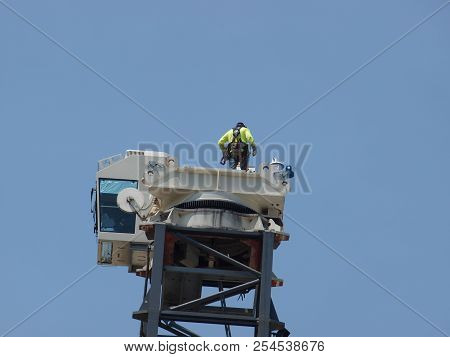 A Worker Stands On The Gear Turntable Of A Tower Crane As The Bridge Boom He Just Released Is Lowere