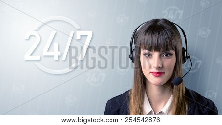 Young female telemarketer with a 24 7 sign next to her