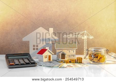 poster of Real estate or property development. Construction business investment concept. Home mortgage loan rate. Coin stack on international banknotes with calculator, house and crane models on the table.