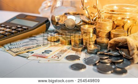 Calculator With Coins Stack And Spilling Out Of Money Bag, Dollar And Euro Banknotes On The Table. C