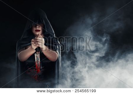 Witch Woman Holding A Bloody Knife With Smoky Background. Halloween Concept