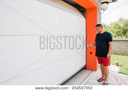 Garage Door Pvc. Man Use Remote Controller For Closing And Opening Garage Door