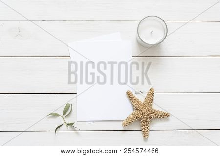 Flat lay with card blank space, stationary, candle, leaves, starfish. Ready to insert your text, invitation, wedding or logo. Best for social media, backgrounds, headers, blogs, wedding poster