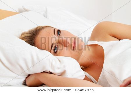 woman lies awake in bed.