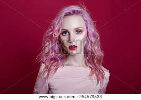 Portrait Of A Woman With Bright Colored Flying Hair, All Shades Of Pink Purple. Hair Coloring, Beaut