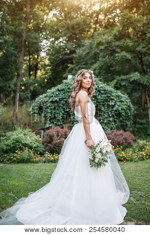 A Cute Curly Woman In A White Wedding Dress With A Wedding Bouquet And Wreath In Her Hair Standing B