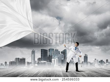 Conceptual Image Of Successful Doctor On White Medical Suit Pulling White Curtain While Standing Out