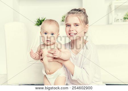 Portrait of a pre-teen girl with his little sister at home. Family concept.