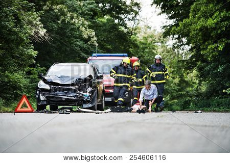 Firefighters Running To Rescue A Woman Lying Unconscious On The Road After A Car Accident.