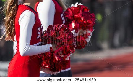 Two High School Cheerleaders With Red And White Pompoms Are Watching The Football Game Ready To Chee