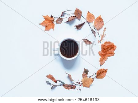 Autumn background - cup of coffee and various dry autumn leaves on the white background. Autumn still life. Autumn composition with concept of spending autumn time at cozy home