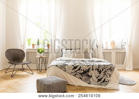 Comfy Bedroom Interior With A Leaf Motif Bedding On A Bed, A Rattan Chair And A Black And White Pouf