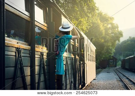 Traveler Girl Leaving The Station By Train. Young Traveler Girl In Vacation. Girl Traveling By Train