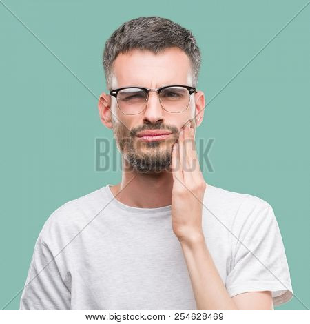 Young tattooed adult man touching mouth with hand with painful expression because of toothache or dental illness on teeth. Dentist concept.