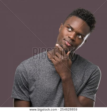 Young african american man wearing grey t-shirt with hand on chin thinking about question, pensive expression. Smiling with thoughtful face. Doubt concept.