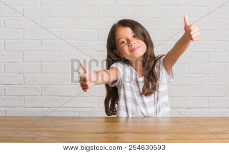Young hispanic kid sitting on the table at home approving doing positive gesture with hand, thumbs up smiling and happy for success. Looking at the camera, winner gesture.