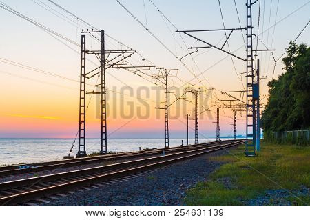 Beautiful Landscape Of A Railroad And Towers Of Traction Line On The Background Of The Sea At Twilig