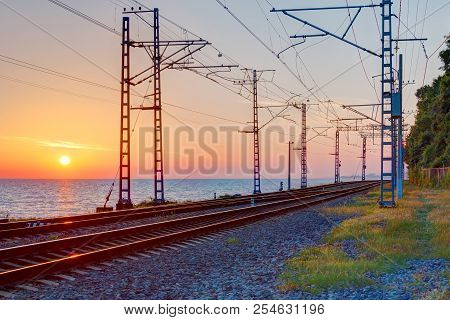 Beautiful Landscape Of A Railroad And Towers Of Traction Line On The Background Of The Sea At Sunset