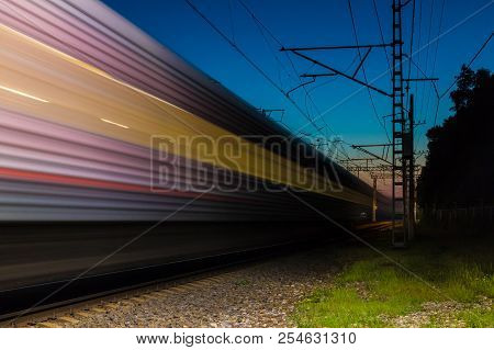 An Illuminated Railroad With A Train In Motion Blur At Dusk, Sochi, Russia