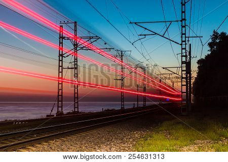 Beautiful Landscape Of A Railroad With Motion Blurred Train On The Background Of The Sea At Twilight