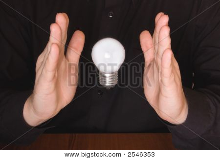 Flying Electrical Bulb Between Palms