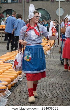 Alkmaar, Netherlands - June 01, 2018: Cheese girl, kaasmeisje, in traditional costume is selling cheese samples at the Alkmaar cheese market