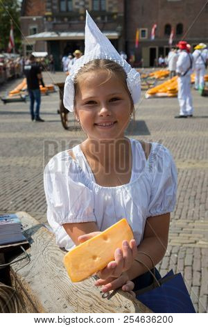 Alkmaar, Netherlands - July 20, 2018: Cheese girl, kaasmeisje, in traditional costume is showing a cheese sample at the Alkmaar cheese market