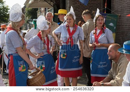 Alkmaar, Netherlands - July 20, 2018: Cheese girls, kaasmeisjes, in traditional costume waiting for the Alkmaar cheese market to start