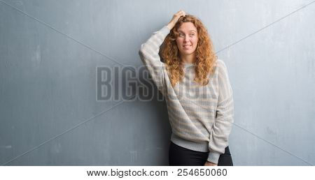 Young redhead woman over grey grunge wall confuse and wonder about question. Uncertain with doubt, thinking with hand on head. Pensive concept.