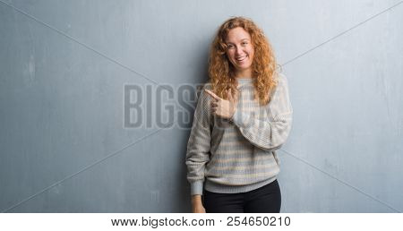 Young redhead woman over grey grunge wall cheerful with a smile of face pointing with hand and finger up to the side with happy and natural expression on face looking at the camera.