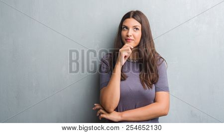 Young brunette woman over grunge grey wall serious face thinking about question, very confused idea