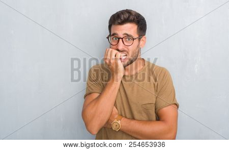 Handsome young man over grey grunge wall wearing glasses looking stressed and nervous with hands on mouth biting nails. Anxiety problem.