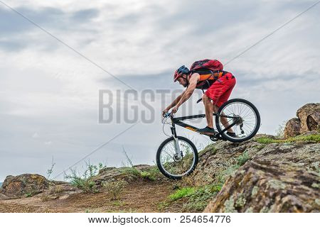 Cyclist In A Helmet And With A Backpack Riding Down The Rock On A Mountain Bike, An Active Lifestyle