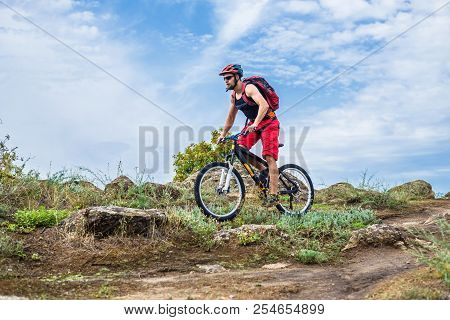 Cyclist On A Mountain Bike Riding On The Rock, Free Space For Your Text.