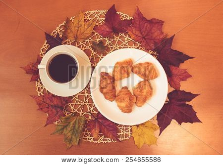 Cup Of Coffee With Croissants And Autumn Maple Leaves On Wooden Table. Top View.