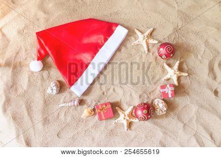 Santa Claus Hat, Christmas Balls, Gifts, Seashells And Starfishes On Sand Beach