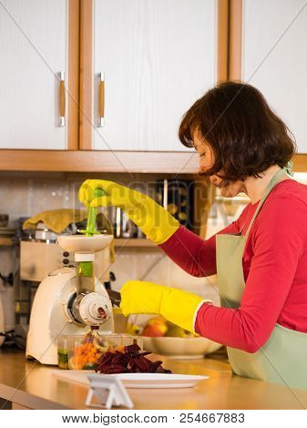 Woman Adding Different Vegetables Red And Green In Juicer Maker. Housewife In Kitchen Making Raw Jui