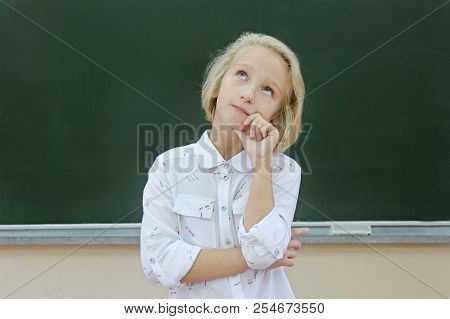 Adorable Blond Kid Girl Thoughtful In A Classroom Near A Chalkboard. The Child Is Focused And Attent