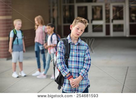 Sad boy feeling left out, teased and bullied by his classmates. Unhappy boy having problems fitting in with others at school