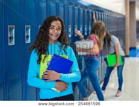 Junior High school Student smiling in a school hallway. Black Female school girl smiling and having fun together during a break at school standing by her locker