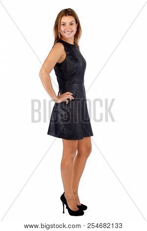 Beautiful Young Woman In Black Leather Dress Standing Sideways And Looking At Camera. Full Body Leng